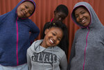 Lilitha Jiphethu, 11, poses for a photo with her friends outside her home in Orange Farm, South Africa, on Tuesday, April 28, 2020. She prefers singing to drawing and chooses to sing a church song in her first language, Xhosa, as her way of describing the future after the pandemic. She misses her choir but takes comfort in the song's lyrics. (AP Photo/Denis Farrell)
