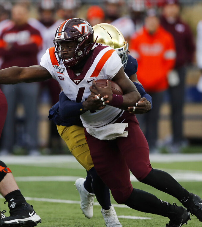 Virginia Tech quarterback Quincy Patterson II (4) is brought down by Notre Dame linebacker Asmar Bilal during the first half of an NCAA college football game, Saturday, Nov. 2, 2019, in South Bend, Ind. (AP Photo/Carlos Osorio)