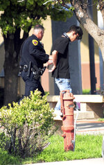 FILE - In this Aug. 28, 2017, file photo, police take Nathaniel Jouett into custody after a shooting at a public library in the eastern New Mexico community of Clovis. Nathaniel Jouett was convicted as an adult to two life sentences that will run concurrently plus 40 years in prison for carrying out the 2017 shooting at the Clovis library, killing two people under a sentence imposed Friday, Feb. 15, 20190, by a state district judge. (Tony Bullocks/The Eastern New Mexico News via AP, File)