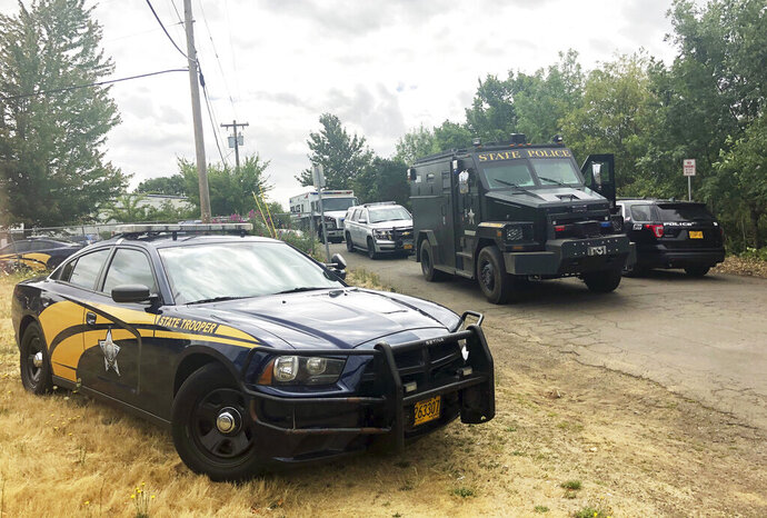 Police vehicles stand outside the scene of a shooting at a Foster Farms plant in Corvallis, Ore., on Thursday, July 18, 2019. Authorities say a man with a handgun opened fire before surrendering. Corvallis Police Capt. Nick Hurley said there were no injuries. (AP Photo/Sarah Zimmerman)