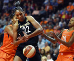 FILE - In this May 20, 2018, file photo, Las Vegas Aces forward A'ja Wilson (22) tries to get a rebound between Connecticut Sun forward Alyssa Thomas, left, and guard Courtney Williams during a WNBA basketball game in Uncasville, Conn. Las Vegas will have a lot of their hometown players to root for at the WNBA All-Star Game on July 27. Reigning rookie of the year A'ja Wilson is one of the team captains. She'll be joined by Aces teammates Liz Cambage and Kayla McBride in the starting lineup.  (Sean D. Elliot/The Day via AP, File)