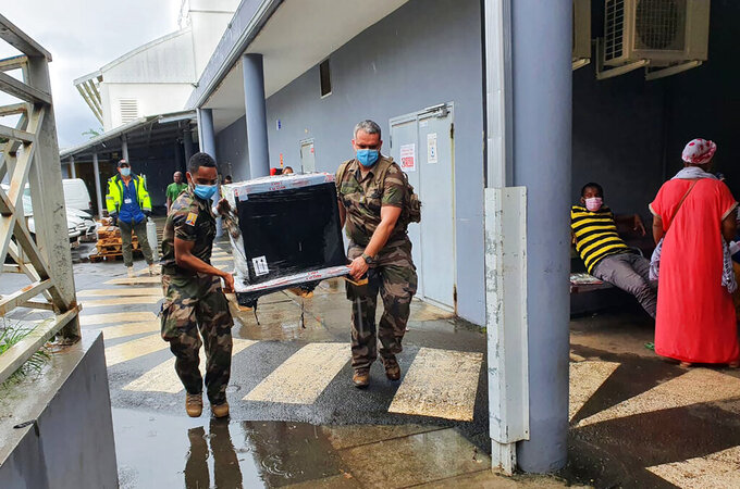 This photo provided by the French Army (EMA) shows soldiers carrying medical relief at Mayotte hospital, Monday, Feb.8, 2021. The French army is sending relief to the French Indian Ocean territory of Mayotte, but some in Mayotte fear it's too little, too late for a region where masks are a luxury and where nearly a third of the population has no running water. (Etat Major des Armees via AP)