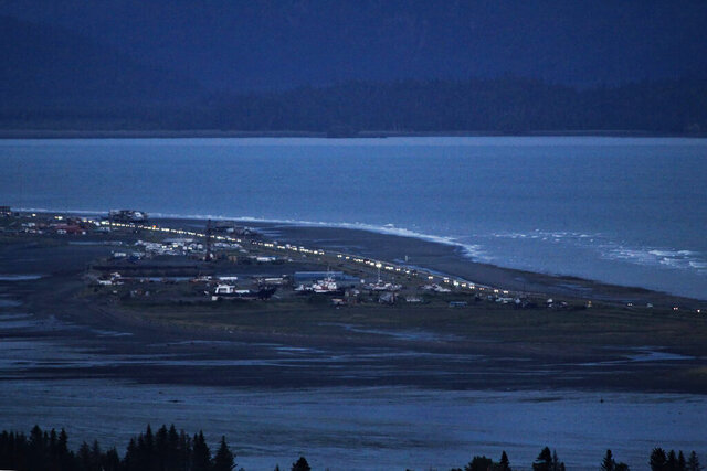 Headlights from a line of cars shine at dusk as people evacuate the Spit in Homer, Alaska, following a powerful earthquake in the Aleutian Islands that prompted a tsunami warning. There were no immediate reports of damage in the sparsely populated area of the state, and the tsunami warning was later canceled. (Pat Williams Russell via AP)