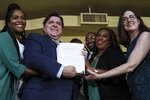 Gov. J. B. Pritzker holds a bill that legalizes adult-use cannabis in the state of Illinois Tuesday, June 25, 2019 at Sankofa Cultural Arts and Business Center in Chicago. Illinois becomes the 11th to legalize the adult-use of recreational marijuana. (AP Photo/Amr Alfiky)