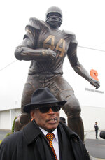 FILE - In this Nov. 14, 2015 file photo, Floyd Little, stands next to a statue of himself dedicated during a ceremony on the Syracuse University campus in Syracuse, N.Y. Little, the Hall of Fame running back who starred at Syracuse and for the Denver Broncos, has died.  The Pro Football Hall of Fame said he died Friday, Jan. 1, 2021.   (AP Photo/Nick Lisi)