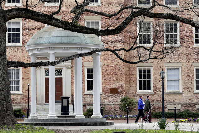 People remove belongings on campus at the University of North Carolina in Chapel Hill, N.C., Wednesday, March 18, 2020. The UNC system announced Tuesday that it would be instructing students to return to their permanent address unless granted an exception to remain in university housing due to the outbreak of the coronavirus. (AP Photo/Gerry Broome)