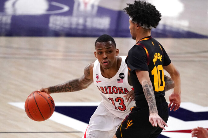 Arizona guard James Akinjo (13) drives against Arizona State guard Jaelen House during the first half of an NCAA college basketball game, Monday, Jan. 25, 2021, in Tucson, Ariz. (AP Photo/Rick Scuteri)