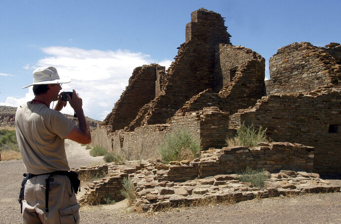 FILE - In this Aug. 10, 2005, file photo, tourist Chris Farthing from Suffolks County, England, takes a picture while visiting Chaco Culture National Historical Park in northwestern New Mexico. Native American leaders are banding together to pressure U.S. officials to ban oil and gas exploration around a sacred tribal site that features massive stone structures and other remnants of an ancient civilization. Tribes are gathering Thursday, March 21, 2019, to face the Trump administration's pro-drilling stance as they push for further protections surrounding Chaco Culture National Historical Park. Federal officials are revamping the management plan for the area around the world heritage site in New Mexico. (AP Photo/Jeff Geissler, File)