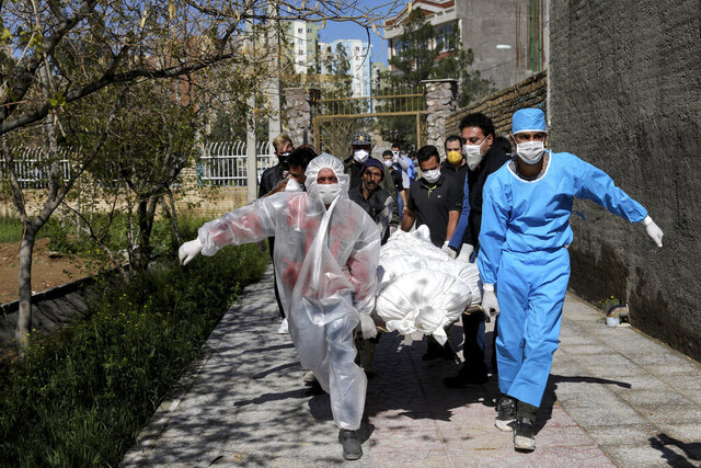 FILE — In this March 30, 2020 file photo, people wearing protective clothing carry the body of a victim who died after being infected with the new coronavirus at a cemetery just outside Tehran, Iran. Even as both face the same invisible enemy in the coronavirus pandemic, Iran and the U.S. remain locked in retaliatory pressure campaigns that now view the outbreak as just the latest battleground. (AP Photo/Ebrahim Noroozi, File)