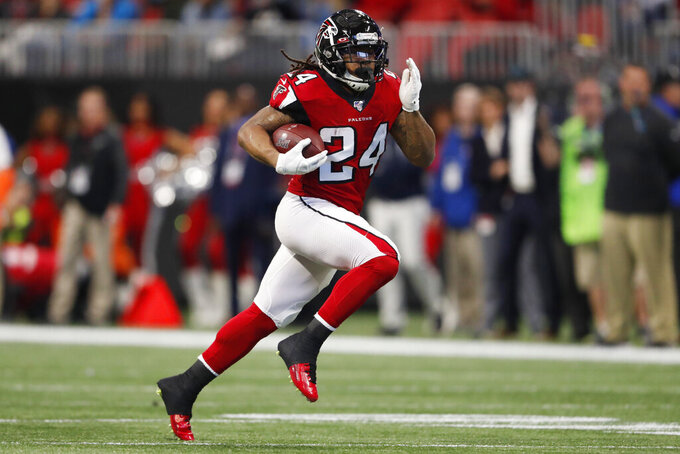 Atlanta Falcons running back Devonta Freeman (24) runs against the Carolina Panthers during the first half of an NFL football game, Sunday, Dec. 8, 2019, in Atlanta. (AP Photo/John Bazemore)