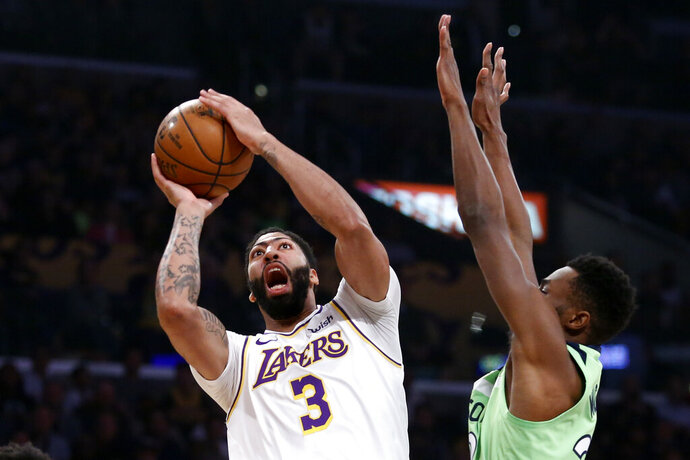 Los Angeles Lakers' Anthony Davis (3) shoots under pressure from Minnesota Timberwolves' Andrew Wiggins (22) during the first half of an NBA basketball game, Sunday, Dec. 8, 2019, in Los Angeles. (AP Photo/Ringo H.W. Chiu)