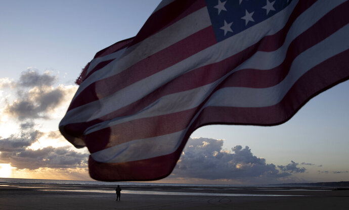 A man in a vintage US WWII uniform walks at sunrise prior to a D-Day 76th anniversary ceremony in Saint Laurent sur Mer, Normandy, France, Saturday, June 6, 2020. Due to coronavirus measures many ceremonies and memorials have been cancelled in the region with the exception of very small gatherings. (AP Photo/Virginia Mayo)