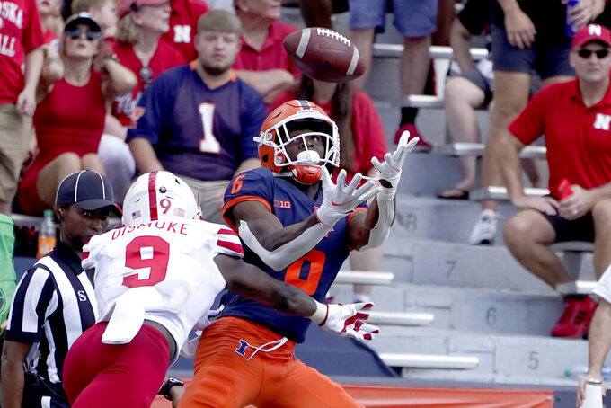Illinois's Deuce Spann catches a 45-yard pass from quarterback Artur Sitkowski as Nebraska safety Marquel Dismuke defends during the second half of an NCAA college football game Saturday, Aug. 28, 2021, in Champaign , Ill. Illinois won 30-22. (AP Photo/Charles Rex Arbogast)