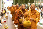 Buddhist monks arrive for a ceremony to reopen the Terminal 21 shopping mall in Nakhon Ratchasima, Thailand, Thursday, Feb. 13, 2020. The worst-ever mass shooting in the country took place at the shopping mall over the weekend. (AP Photo/Sakchai Lalit)