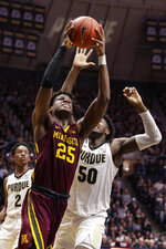 Minnesota center Daniel Oturu (25) shoots in front of Purdue forward Trevion Williams (50) during the first half of an NCAA college basketball game in West Lafayette, Ind., Thursday, Jan. 2, 2020. (AP Photo/Michael Conroy)