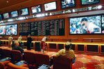 In this Monday, May 14, 2018 photo, people make bets in the sports book at the South Point hotel and casino in Las Vegas. Now that the U.S. Supreme Court has cleared the way for states to legalize sports betting, the race is on to see who will referee the multi-billion-dollar business expected to emerge from the decision.  (AP Photo/John Locher)