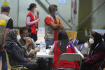 Afghans sit with a Red Cross worker in a COVID testing center after arriving on a Spanish Air Force plane carrying Spanish nationals and Afghans at the Torrejon military base as part of the evacuation process in Madrid, Spain, Thursday, Aug. 19, 2021. (AP Photo/Paul White)