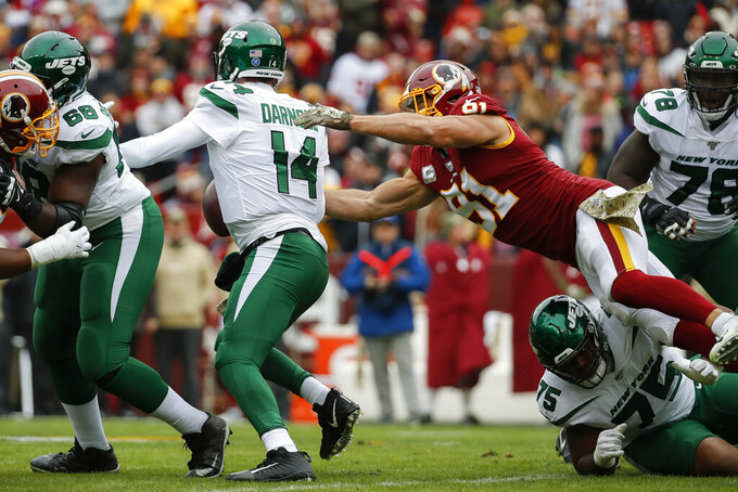 Washington Redskins outside linebacker Ryan Kerrigan (91) causes New York Jets quarterback Sam Darnold (14) to fumble in the first half of an NFL football game, Sunday, Nov. 17, 2019, in Landover, Md. (AP Photo/Alex Brandon)