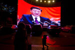 FILE.- In this Dec. 3, 2018, file photo, a child walks past a large screen showing Chinese President Xi Jinping near a carpark in Kashgar, western China's Xinjiang region. Across the Xinjiang region, a growing number of internment camps have been built, where by some estimates 1 million Muslims have been detained, forced to give up their language and their religion and subjected to political indoctrination. Confidential documents, leaked to a consortium of news organizations, lay out the Chinese government's deliberate strategy to lock up ethnic minorities to rewire their thoughts and even the language they speak.(AP Photo/File)
