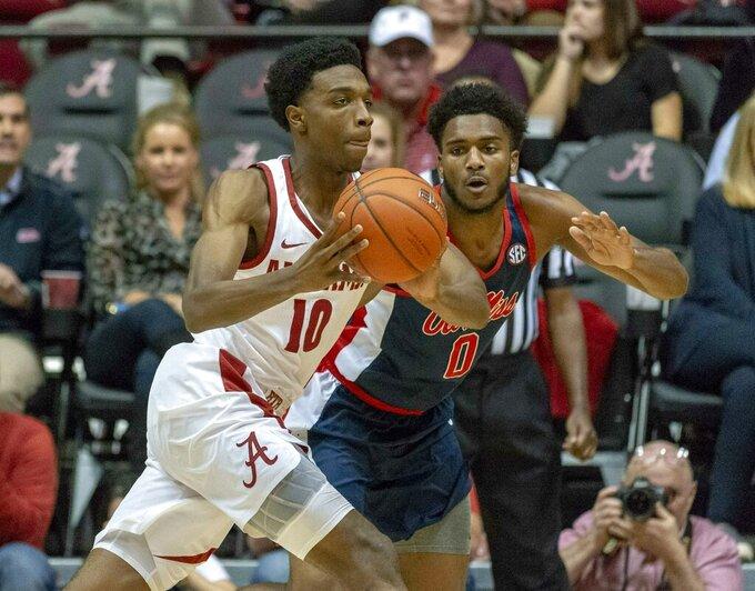 Alabama guard Herbert Jones (10) works by Mississippi guard/forward Blake Hinson (0) during the first half of an NCAA college basketball game, Tuesday, Jan. 22, 2019, in Tuscaloosa, Ala. (AP Photo/Vasha Hunt)