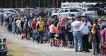 "In this Saturday, May 23, 2020 photo, hundreds of race fans wait in line to purchase tickets at the Ace Speedway on in the rural Alamance County community of Altamahaw near Elon, N.C. North Carolina Gov. Roy Cooper's administration has ordered closed a small stock-car track that's allowed large crowds to gather repeatedly for weekend races well above COVID-19 limits for mass gatherings. Cooper's health secretary says Ace Speedway in Alamance County is an ""imminent hazard"" for the virus' spread and can't reopen unless it creates a safety plan to keep fans away. (Robert Willett/The News & Observer via AP)"