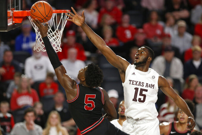 Georgia's Anthony Edwards (5) takes a shot as Texas A&M forward Jonathan Aku (15) defends during an NCAA basketball game in Athens, Ga., on Saturday, Feb. 1, 2020. (Joshua L. Jones/Athens Banner-Herald via AP)