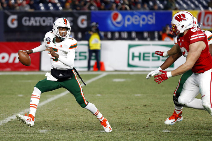 Miami quarterback N'Kosi Perry (5) looks to pass under pressure from Wisconsin defensive end Matt Henningsen (92) during the second half of the Pinstripe Bowl NCAA college football game Thursday, Dec. 27, 2018, in New York. Wisconsin defeated Miami 35-3. (AP Photo/Adam Hunger)