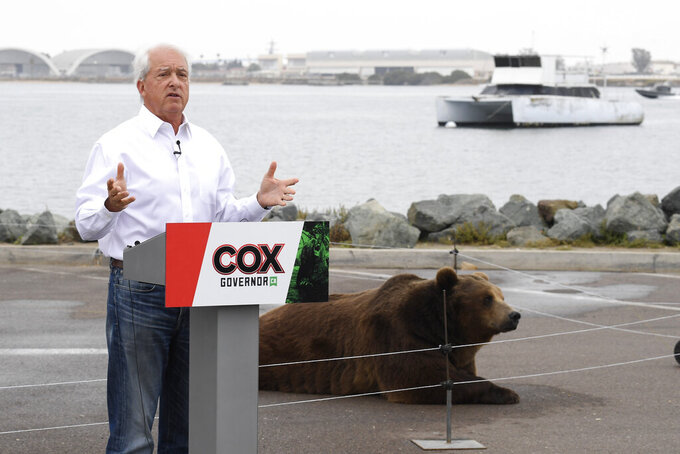 File -- In this May 11, 2021, file photo California gubernatorial candidate John Cox speaks in front of his Kodiak bear at a campaign event held on Shelter Island in San Diego. Cox, a Republican, is among the more than three dozen people who have filed the required paperwork to run in the Sept. 14 recall election that could remove Gov. Gavin Newsom from office. (AP Photo/Denis Poroy, File)