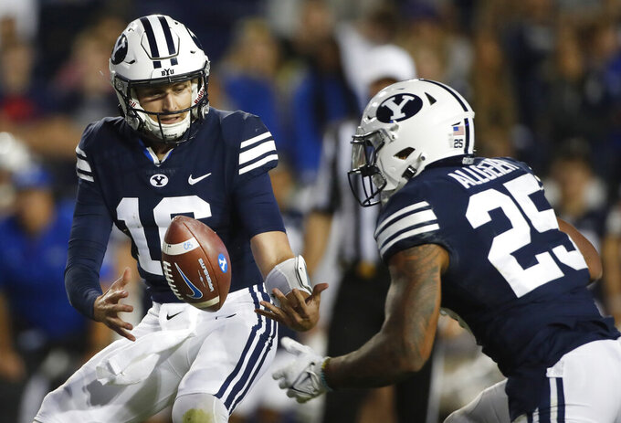 BYU quarterback Baylor Romney (16) fumbles the snap as BYU running back Tyler Allgeier (25) looks to help in the second half of an NCAA college football game against South Florida Saturday, Sept. 25, 2021, in Provo, Utah. (AP Photo/George Frey)