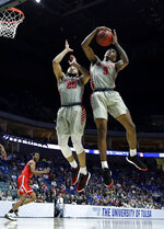 Houston's Galen Robinson Jr. (25) and Armoni Brooks (3) get a rebound during the second half of a second round men's college basketball game against Ohio State in the NCAA Tournament Sunday, March 24, 2019, in Tulsa, Okla. Houston won 74-59. (AP Photo/Charlie Riedel)