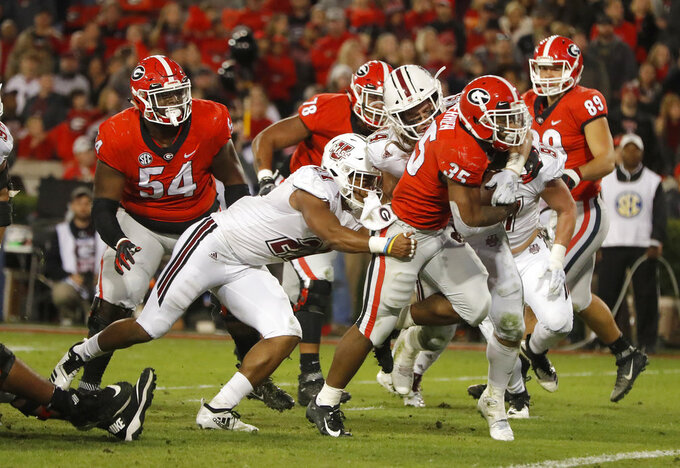 Georgia running back Brian Herrien (35) fights his way into the end zone for a touchdown as Massachusetts cornerback Elijah Johnson (27) and linebacker Bryton Barr (44) hang on during the second half of an NCAA college football game Saturday, Nov. 17, 2018, in Athens, Ga. Georgia wo 66-27. (AP Photo/John Bazemore)