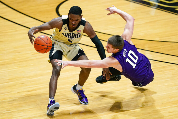 Northwestern forward Miller Kopp (10) dives for the ball with Purdue guard Brandon Newman (5) during the first half of an NCAA college basketball game in West Lafayette, Ind., Saturday, Feb. 6, 2021. (AP Photo/Michael Conroy)