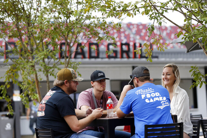 Fans enjoy some food in the new garage facilities during practice for the NASCAR Cup Series auto race at Talladega Superspeedway, Saturday, Oct 12, 2019, in Talladega, Ala. (AP Photo/Butch Dill)