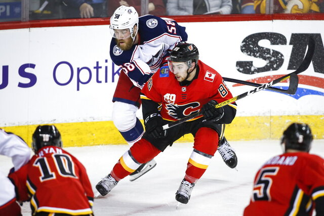 Columbus Blue Jackets' David Savard, , left, scrambles to get past Calgary Flames' Andrew Mangiapane during the second period of an NHL hockey game, Wednesday, March 4, 2020 in Calgary, Alberta. (Jeff McIntosh/The Canadian Press via AP)