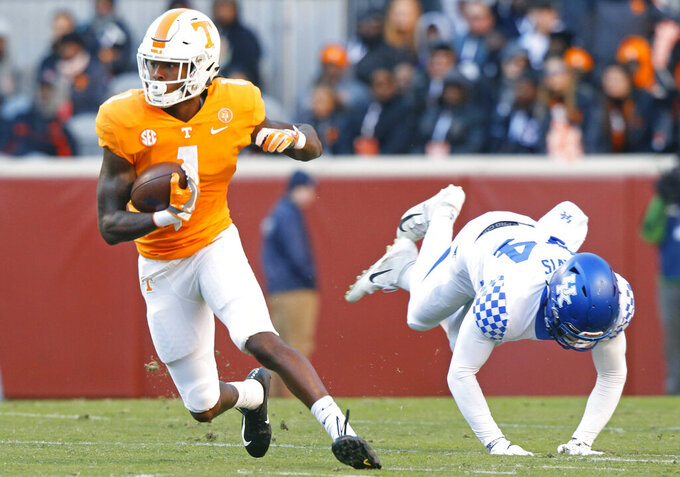FILE - In this Nov. 10, 2018, file photo, Tennessee wide receiver Marquez Callaway (1) escapes from Kentucky linebacker Jamin Davis (44) in the first half of an NCAA college football game in Knoxville, Tenn. Tennessee's wide receivers savor the opportunity to play for their new position coach because they appreciate what Tee Martin accomplished during his own playing career. Martin was the starting quarterback on Tennessee's 1998 national championship team and is back at his alma mater trying to help the Volunteers become competitive again in the Southeastern Conference. (AP Photo/Wade Payne, File)
