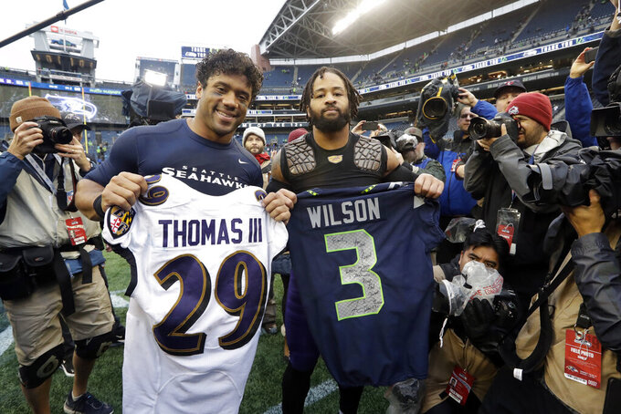 Seattle Seahawks quarterback Russell Wilson, left, and Baltimore Ravens free safety Earl Thomas, right, pose for a photo after they traded jerseys following an NFL football game, Sunday, Oct. 20, 2019, in Seattle. (AP Photo/Elaine Thompson)