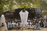 Muslims make traditional Friday prayers in front of a police riot truck, providing security due to the ongoing general threat of attacks by Islamic extremist group Boko Haram, at a mosque near to the Emir's palace in Kano, northern Nigeria, Friday, Feb. 15, 2019. Nigeria is due to hold general elections on Saturday, pitting incumbent President Muhammadu Buhari against leading opposition presidential candidate Atiku Abubakar. (AP Photo/Ben Curtis)