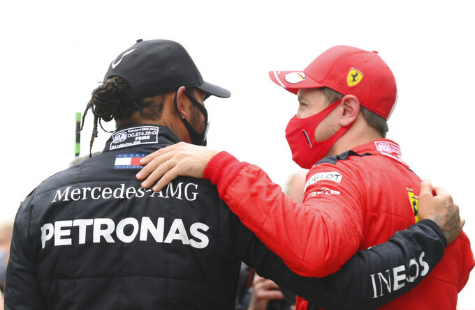 Mercedes driver Lewis Hamilton of Britain, left, speaks with third placed Ferrari driver Sebastian Vettel of Germany after winning the Turkish Formula One Grand Prix at the Istanbul Park circuit racetrack in Istanbul, Sunday, Nov. 15, 2020. (Clive Mason/Pool via AP)
