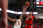 Texas Tech's TJ Holyfield (22) shoots the ball over Texas' Royce Hamm Jr. (5) during the second half of an NCAA college basketball game Saturday, Feb. 29, 2020, in Lubbock, Texas. (AP Photo/Brad Tollefson)