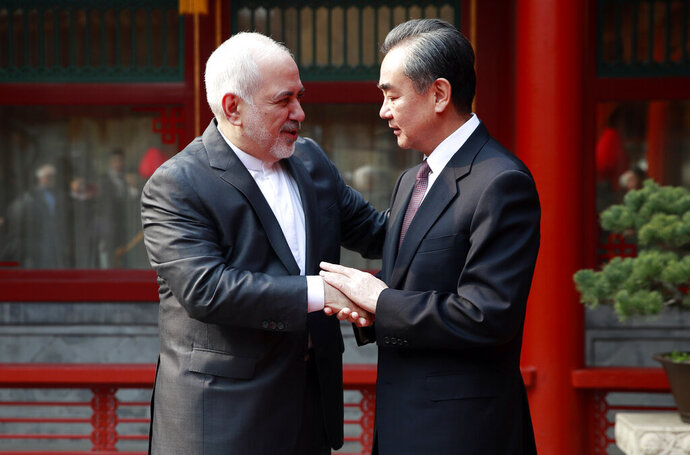 Iranian Foreign Minister Mohammad Javad Zarif, left, and his Chinese counterpart Wang Yi shake hands during their meeting at the Diaoyutai State Guesthouse in Beijing Tuesday, Feb. 19, 2019. (How Hwee Young/Pool Photo via AP)