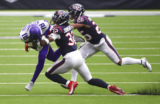 Minnesota Vikings wide receiver Bisi Johnson (81) is hit by Houston Texans cornerback Lonnie Johnson (32) and cornerback Vernon Hargreaves III (26) after a catch during the second half of an NFL football game Sunday, Oct. 4, 2020, in Houston. (AP Photo/Eric Christian Smith)