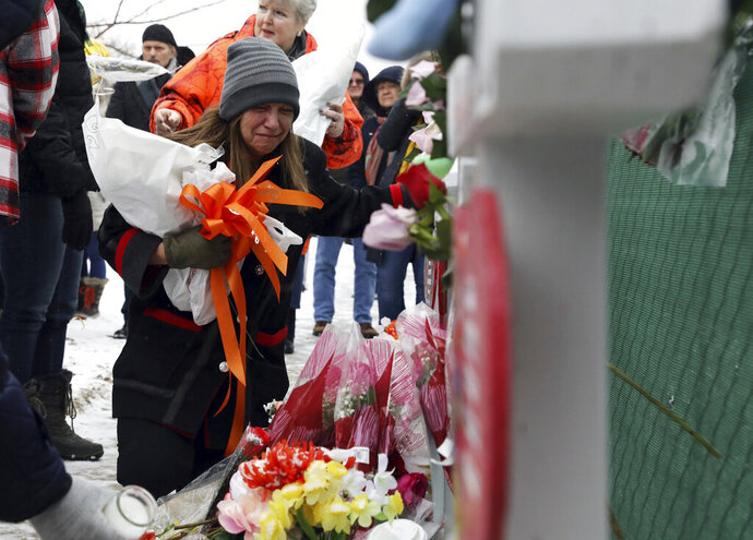 People pray at a makeshift memorial Sunday, Feb. 17, 2019, in Aurora, Ill., near Henry Pratt Co. manufacturing company where several were killed on Friday. Authorities say an initial background check five years ago failed to flag an out-of-state felony conviction that would have prevented a man from buying the gun he used in the mass shooting in Aurora. (AP Photo/Nam Y. Huh)