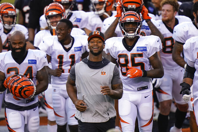 Cincinnati Bengals running back Joe Mixon (28) (center), who didn't dress for play, runs off the field after an NFL football team scrimmage in Cincinnati, Sunday, Aug. 30, 2020. (AP Photo/Bryan Woolston)