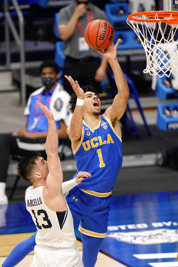 UCLA guard Jules Bernard (1) takes a shot over BYU guard Alex Barcello (13) during the second half of a first-round game in the NCAA college basketball tournament at Hinkle Fieldhouse in Indianapolis, Saturday, March 20, 2021. (AP Photo/AJ Mast)