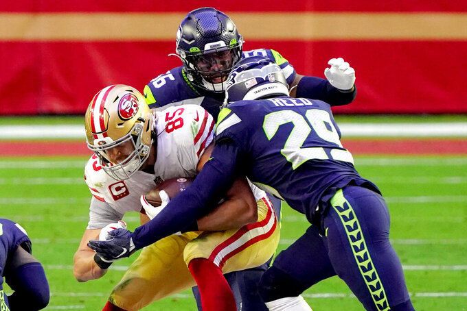 San Francisco 49ers tight end George Kittle (85) is hit by Seattle Seahawks free safety D.J. Reed (29) and linebacker Jordyn Brooks (56) during the second half of an NFL football game, Sunday, Jan. 3, 2021, in Glendale, Ariz. (AP Photo/Rick Scuteri)