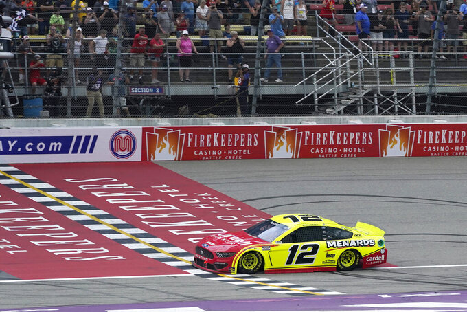 Ryan Blaney takes the checker flag to win the NASCAR Cup Series auto race at Michigan International Speedway, Sunday, Aug. 22, 2021, in Brooklyn, Mich. (AP Photo/Carlos Osorio)