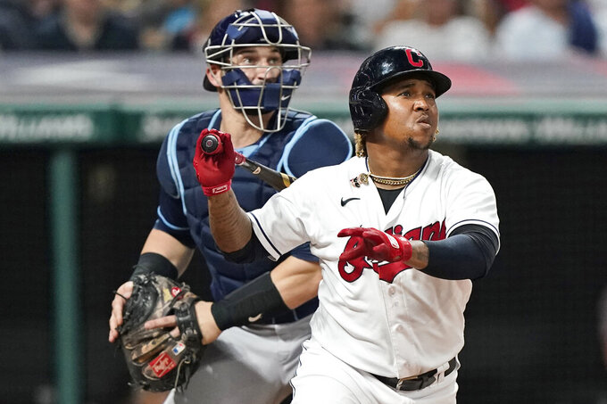 Cleveland Indians' Jose Ramirez, front, and Tampa Bay Rays catcher Mike Zunino watch an RBI triple by Ramirez during the seventh inning of a baseball game, Friday, July 23, 2021, in Cleveland. (AP Photo/Tony Dejak)