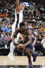 New Orleans Pelicans' Zion Williamson, right, falls as he tangles with San Antonio Spurs' DeMar DeRozan during the first half of an NBA preseason basketball game, Sunday, Oct. 13, 2019, in San Antonio. (AP Photo/Darren Abate)