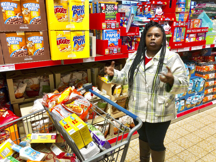 In this Sunday, Feb. 10, 2019 photo, Laquesha Russell, a 36-year-old home health care worker who makes $10.78 an hour, speaks during an interview as she shops for groceries for her four children in Springfield, Ill. Nearly a quarter of workers in Illinois would see their pay almost double under a proposal nearing final approval in the Legislature, but inflation will take a huge bite by the time the state's minimum wage reaches $15 an hour in 2025. Business owners complain that the phase-in is too fast. But Russell said,