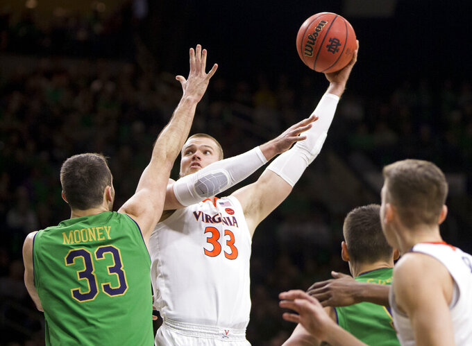 Virginia's Jack Salt, center, goes up for a shot next to Notre Dame's John Mooney, left, during the first half of an NCAA college basketball game Saturday, Jan. 26, 2019, in South Bend, Ind. Virginia won 82-55. (AP Photo/Robert Franklin)